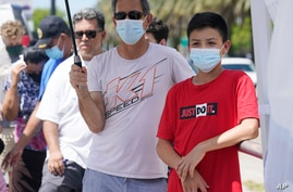 Agustin Cortez, 13, and his uncle, Luis Cortez, wait to get a COVID-19 test for Agustin, Thursday, July 15, 2021, in North…