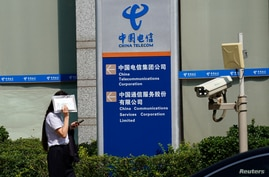 FILE PHOTO: FILE PHOTO: Woman shields herself from the sun as she walks past an office building of China Telecom, in Beijing