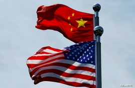 FILE PHOTO: Chinese and U.S. flags flutter near The Bund in Shanghai