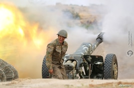 An ethnic Armenian soldier fires an artillery piece during fighting with Azerbaijan's forces in Nagorno-Karabakh