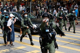 FILE PHOTO: Riot police chase pro-democracy protesters during a demonstration opposing postponed elections, in Hong Kong