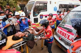 An injured man is carried by rescue workers after protests against the military coup, in Mandalay
