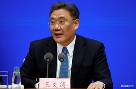 Chinese Commerce Minister Wang Wentao attends a State Council Information Office news conference in Beijing
