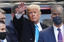 Trump acknowledges people as he gets in his SUV outside Trump Tower in New York City