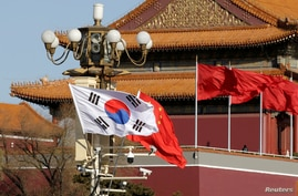 FILE PHOTO: South Korea and China's flags flutter next to Tiananmen Gate in Beijing
