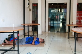 A man sleeps on the terrace of a closed restaurant, as Indonesia imposes emergency measures, in Jakarta