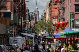 People walk down a street lined with outdoor seating for restaurants in the Little Italy neighborhood of Manhattan, in New York City