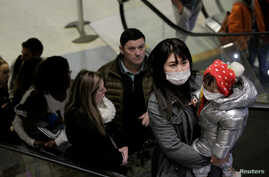 Travellers wearing masks arrive on a direct flight from China, after a spokesman from the U.S. Centers for Disease Control and…