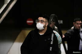 FILE PHOTO: A traveler wearing a mask arrives on a direct flight from China, after a spokesman from the U.S. Centers for…
