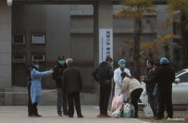 FILE PHOTO: Medical staff and security personnel stop patients' family members from being too close to the Jinyintan hospital,…