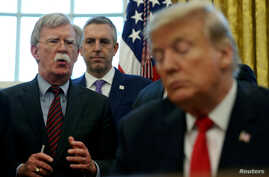 FILE PHOTO: U.S. President Donald Trump listens as his national security adviser John Bolton speaks during a presidential…