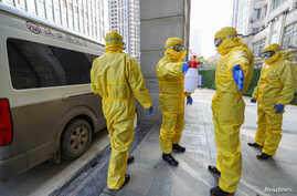 Funeral parlour staff members in protective suits help a colleague with disinfection after they transferred a body at a…