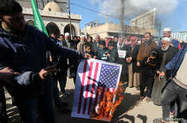 Palestinian demonstrators burn a representation of a U.S. flag during a protest against the U.S. President Donald Trump's…