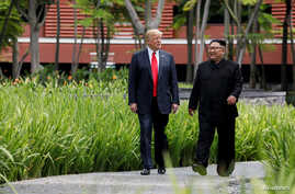 U.S. President Donald Trump and North Korea's leader Kim Jong Un walk together before their working lunch during their summit…
