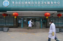 A doctor disinfects the entrance of a community health service center, which has an isolated section to receive patients with…