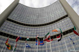 FILE PHOTO: An Iranian flag flutters amongst other flags in front of the International Atomic Energy Agency (IAEA) headquarters…