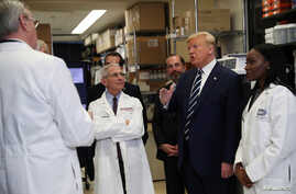 U.S. President Donald Trump is flanked by Director of National Institute of Allergy and Infectious Diseases Anthony Fauci;…