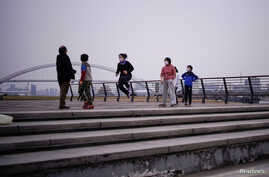 People wearing face masks jump rope at a park, as the country is hit by an outbreak of the novel coronavirus, in Shanghai,…