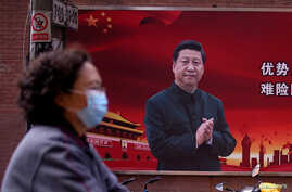 A woman wearing a protective mask is seen past a portrait of Chinese President Xi Jinping on a street as the country is hit by…