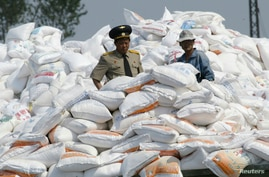 A North Korean military officer (L) stands amid sacks of flour transported from China on the banks of the Yalu River near the…