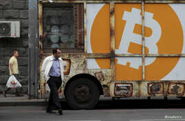 People walk past a board with the logo of Bitcoin in a street in Yerevan, Armenia September 9, 2019. REUTERS/Anton Vaganov