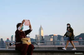 People with protective masks walk in front of Hong Kong's skyline, following the novel coronavirus disease (COVID-19) outbreak,…