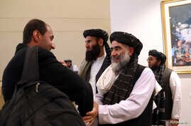 FILE PHOTO: Members of Afghanistan's Taliban delegation (R) gather ahead of an agreement signing between them and U.S…