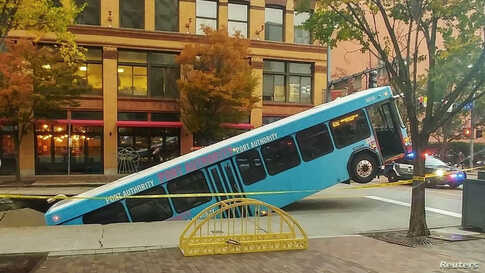 Front of a public bus sticks out of a sinkhole on 10th and Penn Avenue in Pittsburgh, Pennsylvania, U.S., October 28, 2019 in this picture obtained from social media, October 28, 2019.