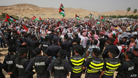 Jordanian police officers surround protesters during a demonstration in solidarity with Palestinians, in the town of Karameh on…