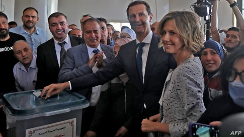 Syrian President Bashar al-Assad (C) and his wife Asma (R) cast their votes at a polling station in Douma, near Damascus on May…