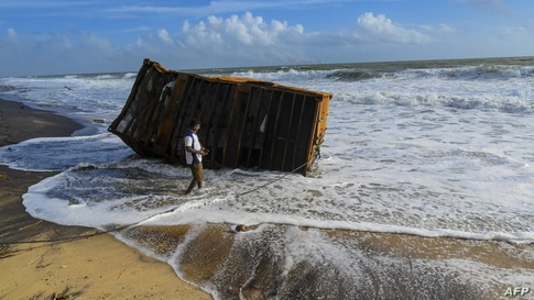 A man stands next to burnt container washed ashore from the Singapore-registered container ship MV X-Press Pearl, which has…