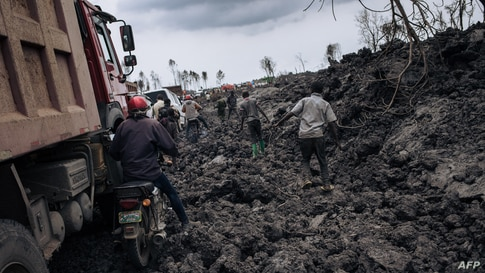 Motorbike drivers and trucks drive through the solidified lava flow of Nyiragongo volcano in the northern neighbourhoods of…
