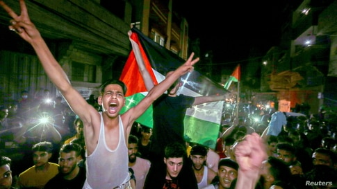 Palestinians celebrate in the streets following a ceasefire, in the southern Gaza Strip May 21, 2021. REUTERS/Ibraheem Abu…