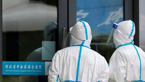 FILE PHOTO: Staff members in protective suits stand at Hubei Provincial Hospital of Integrated Chinese and Western Medicine…