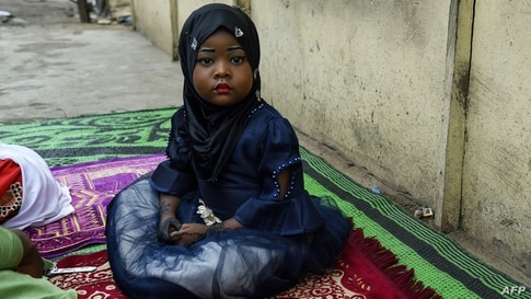 TOPSHOT - A young girl sits on a mat, as worshippers arrive to pray to mark the Muslim Eid-al-Adha (Festival of Sacrifices)…