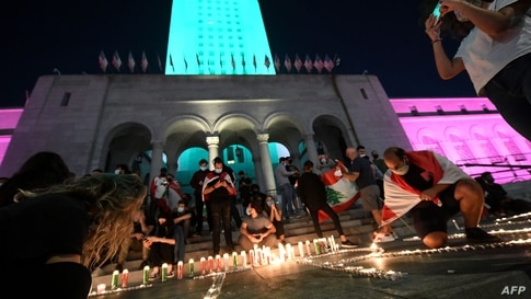 People light candles and gather during a candelight vigil for victims of Beirut's blast in front of the City Hall building…