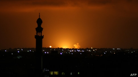 TOPSHOT - Smoke and flames are seen following an Israeli air strike in the Khan Yunis town of the southern Gaza Strip on…