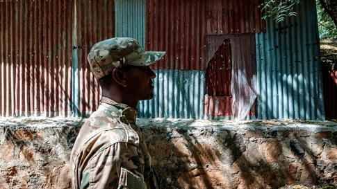 In this picture taken on November 25, 2020, a member of the Amhara Special forces walks in front of a tin wall damaged during…