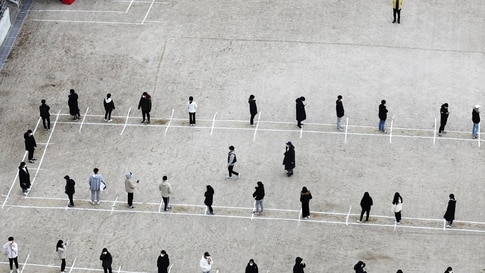Students and staff queue to receive a test for the covid-19 coronavirus at a high school in Sejong city, south of Seoul on…