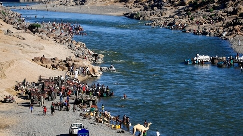 Ethiopian refugees who fled the fighting in the Tigray region gather on the banks of a border river with Sudan, in the Hamdayit…