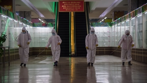 TOPSHOT - Health workers spray disinfectant inside the Pyongyang Department Store No. 1 prior to opening for business, in…