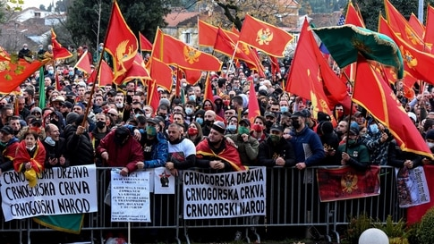 People shout slogans and wave flags of Montenegro during a protest against the new government in Podgorica on December 28, 2020…