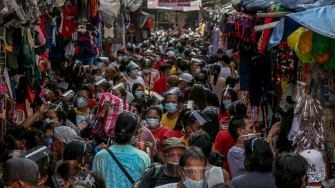 TOPSHOT - People wearing face shields and masks amid the Covid-19 coronavirus pandemic visit a popular shopping market hours…