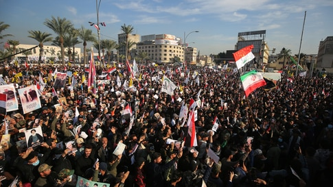 TOPSHOT - Iraqi demonstrators lift flags and placards as they rally in Tahrir square in the capital Baghdad on January 3, 2021,…