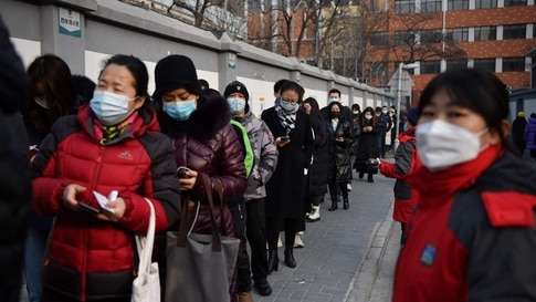 TOPSHOT - People line up to be tested for the Covid-19 coronavirus in Beijing on January 22, 2021, part of a drive to test two…