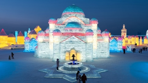 TOPSHOT - People look at ice sculptures at the Harbin Ice and Snow Festival in Harbin, in northeastern China's Heilongjiang…