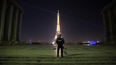 TOPSHOT - A policeman patrols at the Trocadero in front of the illuminated Eiffel Tower during the New Year's Eve as a 8:00 pm…