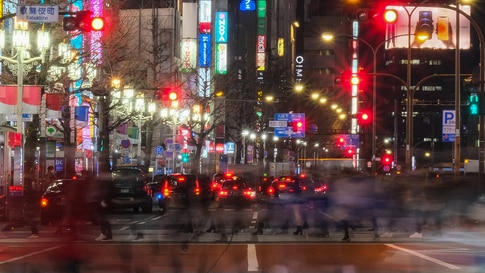 TOPSHOT - Pedestrians cross a street in Tokyo's Shinjuku district on January 13, 2021, as the country expanded the Covid-19…
