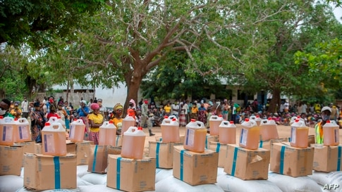 """TOPSHOT - People await the United Nations World Food Program's distribution of food at the """"3 de fevereiro escola"""" school in…"""