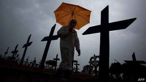 TOPSHOT - A workers wearing a protective suit and carrying an umbrella walks past the graves of COVID-19 victims at the Nossa…